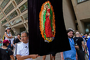 """Daniel Alvarado of Dallas stands next to the image of the Virgin of Gualdaupe he made during the Families Belong Together rally in front of of City Hall in downtown Dallas.Asked about the image, Alvarado responded ;""""It's the standard bearer. It's a symbol. What's going on is horrific. It's time to vote and get ornanized."""""""