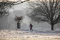 © Licensed to London News Pictures. 18/01/2020. London, UK. A runner in the park as dog walkers and families enjoy a wonderful frosty and misty morning in Richmond Park, London as forecasters predict a cold week ahead. Richmond Park issued a warning for ice after the previous day's high rain fall which could lead to increased slippery conditions for walkers and road users. Photo credit: Alex Lentati/LNP