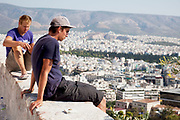 Young men high up on the hill look out over the city from the Acropolis of Athens. The main buildings on the Acropolis were built by Pericles in the fifth century BC as a monument to the cultural and political achievements of the inhabitants of Athens. The term acropolis means upper city and many of the city states of ancient Greece are built around an acropolis where the inhabitants can go as a place of refuge in times of invasion. It's for this reason that the most sacred buildings are usually on the acropolis. It's the safest most secure place in town. As little as 150 years ago there were still dwellings on the Acropolis of Athens. Athens is the capital and largest city of Greece. It dominates the Attica periphery and is one of the world's oldest cities, as its recorded history spans around 3,400 years. Classical Athens was a powerful city-state. A centre for the arts, learning and philosophy.