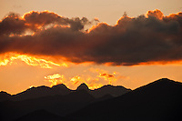 Post-sunset alpenglow lights clouds above silhouetted mountains in the NE region of the Olympic Mountains of western Washington state, USA. Boulder Mountain, Iron Mountain, the Jupiter Hills