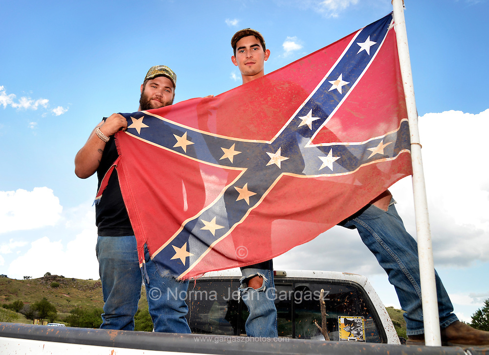 """Sonoita, Arizona, USA, 7th July, 2015:  Caleb Gates, 20, (left), and Ray Helton, 22, display the Confederate flag attached to the truck that Gates was driving in Sonoita, Arizona, USA.  About the flag Gates says, """"It is part of Southern heritage.  I think it means rebellion, not racism.  Some of my best friends are Black and Mexican"""".  Helton says, """"I don't see it as racist"""".  Controversy over the Confederate battle flag has escalated across the southern states after the killings at Emanuel African Methodist Episcopal Church in South Carolina."""