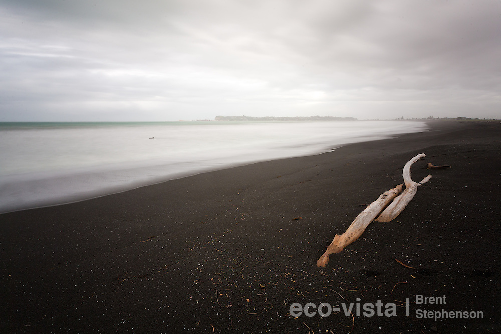 A lone piece of driftwood lies on a black pebble beach, with a storm surge rolling in and Napier Port and Napier Hill in the background. Long exposure with blurred wave action and clouds. Westshore Beach, Hawkes Bay, New Zealand. September.