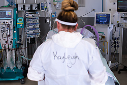 © Licensed to London News Pictures. 05/02/2021. Oldham , UK . Senior Support Worker KAYLEIGH MILLOY (34) stands in front of the bed of an unconscious patient , on the ward . Inside Royal Oldham Hospital's Covid ITU where patients, most of them unconscious , are treated for the effects of Coronavirus . Photo credit : Joel Goodman/LNP