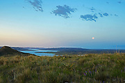 Full moon setting over Fort Peck Reservoir and the Missouri River Breaks at dawn. American Prairie Reserve region of C.M. Russell National Wildlife Refuge south of Malta in Phillips County, Montana.