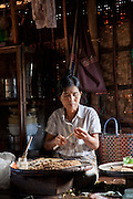 A woman makes a cheroot, a small local cigar, in her workshop (which is her home) in the middle of Inle Lake, Shan state, Myanmar