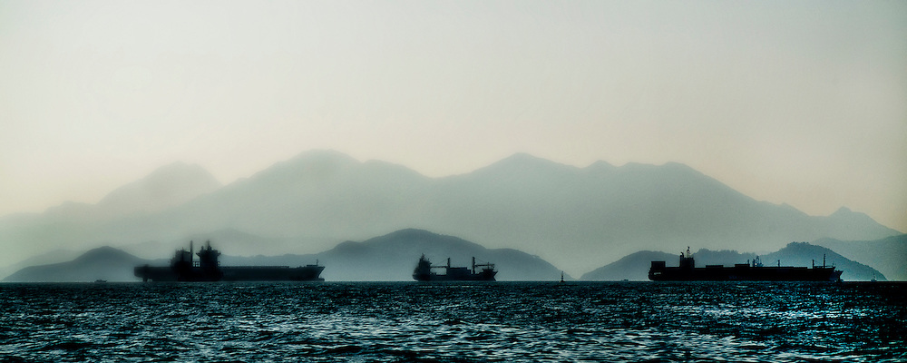 Giant silent freighters glide by Hong Kong harbor in the distance as daily life on the waters closer to shore is a constant mahem of activity.