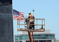 Photographed from the fire escape of the nearby Glikbarg building, a construction worker at the Taylor Building site in Oldtown Salinas is framed by the flag and the star at the top of the National Steinbeck Center.
