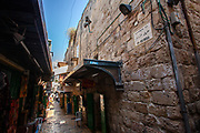 Shops and stalls in an Alley in the Old City, Jerusalem, Israel Street sign in English Hebrew and Arabic