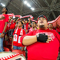 Singapore fans sing the national anthem prior to the group stage match of the AFF Suzuki Cup between Singapore and Malaysia at the National Stadium at the Singapore Sports Hub on November 29, 2014, in Singapore.