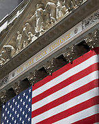 Up view of the exterior of the New York Stock Exchange building with an American Flag