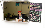 Teen age 17 thoughtfully waiting for customers in her fajita food stand. Grand Old Day Street Fair St Paul Minnesota USA
