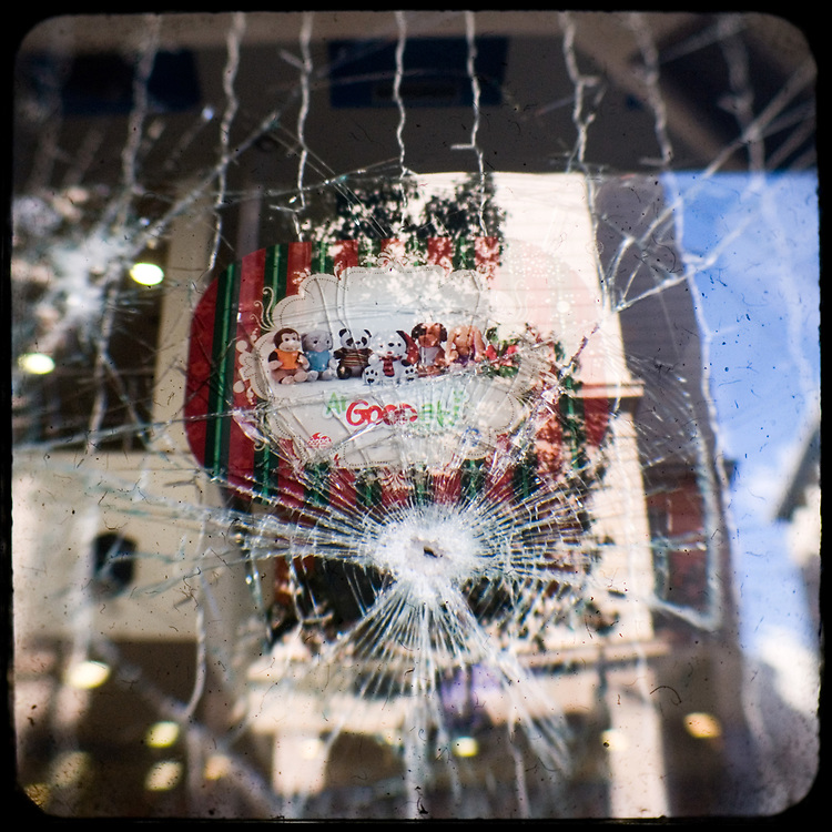 The smashed window of Goody's fast food restaurant in Athens. <br /> <br /> Following the murder of a 15 year old boy, Alexandros Grigoropoulos, by a policeman on 6 December 2008 widespread riots, protests and unrest followed lasting for several weeks and spreading beyond the capital and even overseas<br /> <br /> When I walked in the streets of my town the day after the riots I instantly forgot the image I had about Athens, that of a bustling, peaceful, energetic metropolis and in my mind came the old photographs from WWII, the civil war and the students uprising against the dictatorship. <br /> <br /> Thus I decided not to turn my digital camera straight to the destroyed buildings but to photograph through an old camera that worked as a filter, a barrier between me and the city.