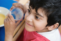 Boy with physical and learning having a drink with his school dinner,