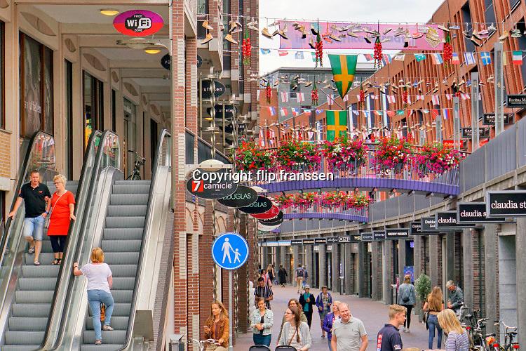 Nederland, Nijmegen, 3-7-2019Aanloop naar de Nijmeegse vierdaagse. Schoenen hangen boven de Marikenstraat, een winkelstraat in de binnenstad. de groene oranje vlag is de vierdaagsevlag en de bloemen zijn de gladiolen die de lopers krijgen als ze de finish halen.Foto: Flip Franssen