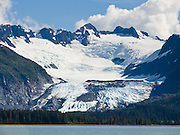 Glaciers pour from the steep and glaciated Chugach Mountains into Prince William Sound, Alaska, USA. Prince William Sound is surrounded by Chugach National Forest (the second largest national forest in the USA). Tour spectacular Prince William Sound by commercial boat from Whittier, which sits strategically on Kenai Peninsula at the head of Passage Canal. Whittier is a port for the Alaska Marine Highway System, a ferry service which operates along the south-central coast, eastern Aleutian Islands, and the Inside Passage of Alaska and British Columbia, Canada. Cruise ships stop at the port of Whittier for passenger connections to Anchorage (by road 60 miles) and to the interior of Alaska via highway and rail (the Denali Express). Known by locals as the Whittier tunnel or the Portage tunnel, the Anton Anderson Memorial Tunnel links Whittier via Portage Glacier Highway to the Seward Highway and Anchorage. At 13,300 feet long (4050 m), it is the longest combined rail and highway tunnel in North America. Whittier was severely damaged by tsunamis triggered by the 1964 Good Friday Earthquake, when thirteen people died from waves reaching 43 feet high (13 meters).