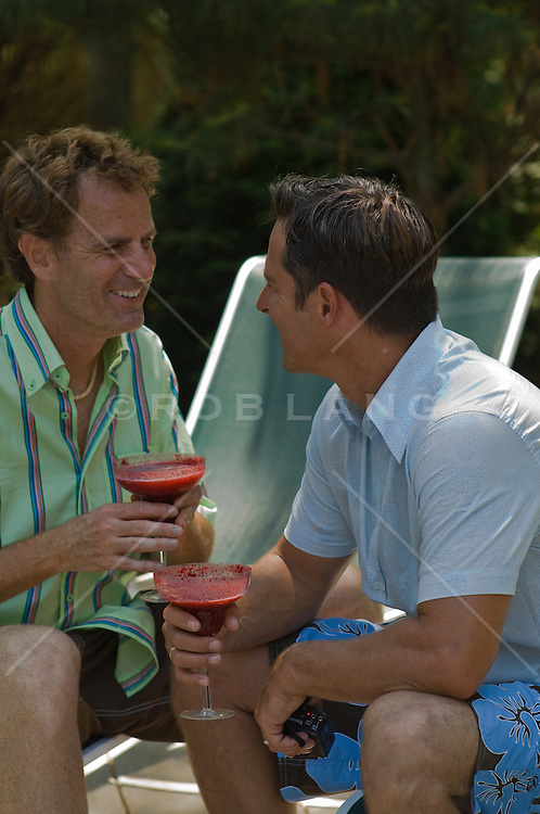 Two men enjoying a tropical drink outside on lounge chairs