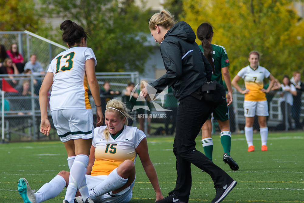 Head Athletic Therapist, Nicole Renneberg, runs to 5th year defender Racquel Marshall (15) of the Regina Cougars who's was shaken up after a play during the Women's Soccer Homeopener on September 10 at U of R Field. Credit: Arthur Ward/Arthur Images