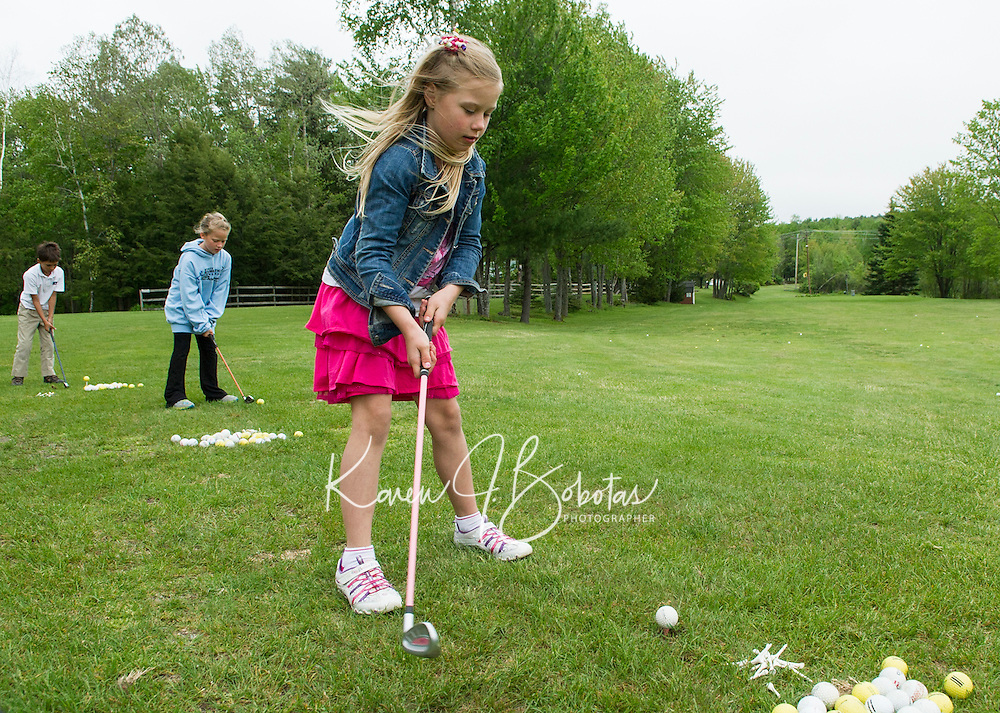 Camryn Marshall takes a practice swing during golf lessons with Randy Annis at Bolduc Park Tuesday evening.  (Karen Bobotas/for the Laconia Daily Sun)