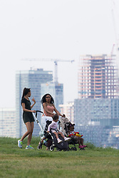 Two women push their baby buggies in the hazy sunshine partially obscures the Docklands skyline in London, seen from Maze Hill, Greenwich as Mayor Sadiq Khan announces air toxicity alerts for the Capital. London, May 08 2018.