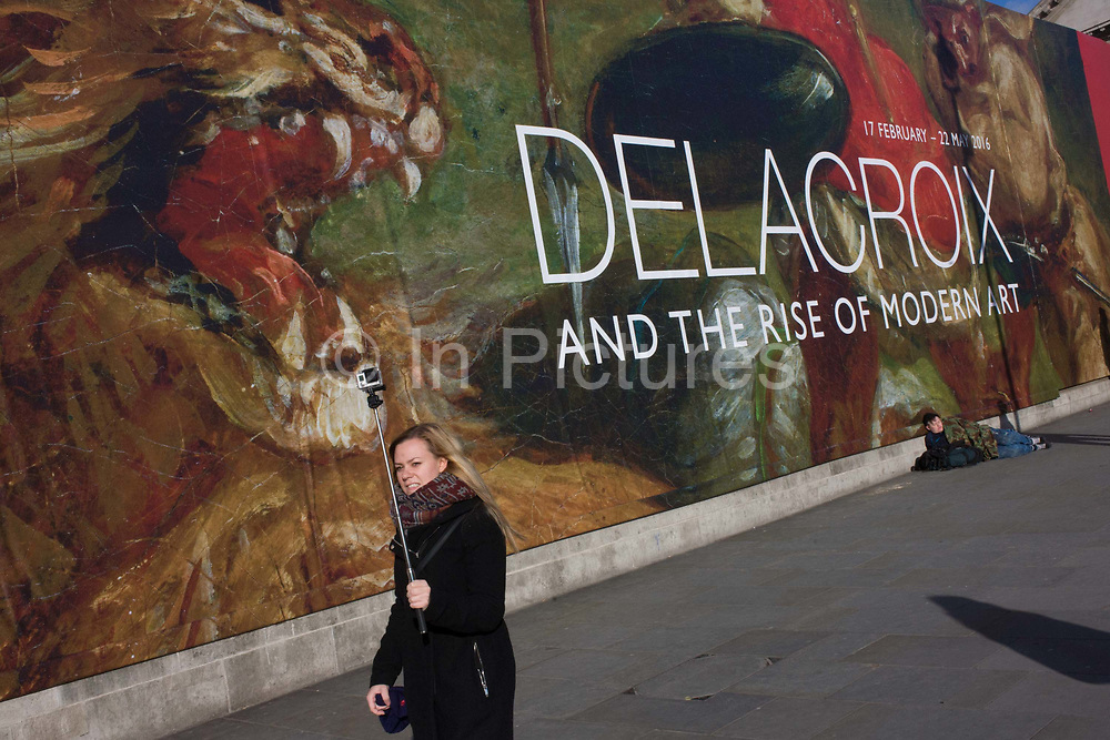 A woman and her selfie stick stands in front of the broad message on a hoarding announcing the next major exhibition by Delacroix at the National Gallery in London. As a scene of the classic and contemporary Art and Culture, we see the two juxtaposed on the pavement of a modern capital city. In the background is a homeless man, seemingly asleep on the ground, beneath the large lettering announcing the major exhibition. Ferdinand Victor Eugène Delacroix (1798 – 1863) was a French Romantic artist regarded from the outset of his career as the leader of the French Romantic school