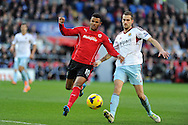 Cardiff city's Fraizer Campbell (l) holds off West Ham's Roger Johnson .Barclays Premier league, Cardiff city v West Ham Utd match at the Cardiff city Stadium in Cardiff, South Wales on Saturday 11th Jan 2014.<br /> pic by Andrew Orchard, Andrew Orchard sports photography.