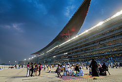 Spectators and grandstand at horse racing meeting at Al Meydan racecourse at night in Dubai United Arab Emirates