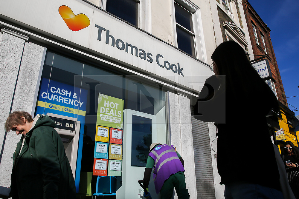 © Licensed to London News Pictures. 23/09/2019. London, UK. A street cleaner picks up the rubbish outside the branch of Thomas Cook in central London. The Civil Aviation Authority (CAA) announced shortly after 2 am this morning that the travel agent firm Thomas Cook hadceased trading with immediate effect. The liquidation puts 9,000 British jobs at risk and leaves the UK Government and CAA to fly home around 150,000 British holiday-makers left stranded around the world. Photo credit: Dinendra Haria/LNP