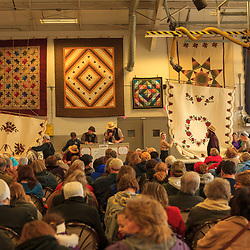 An Amish auction eer sells quilts to raise funds for the Bart Volunteer Fire Company at the annual mud sale in Lancaster County, Pennsylvania.