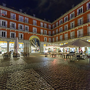 Madrid, Spain - February 14, 2018 - The Plaza Mayor at Night. An incredible public space in Spain's capital city of Madrid. The plaza's history traces back to the 15th century and was used as the main market of the town. Several architects have been credited with it's design and construction over the years. After a massive fire in 1790, Plaza Mayor's current design can be credited to Juan de Villanueva.<br /> <br /> Image: © Rod Mountain http://www.rodmountain.com http://bit.ly/RM-archive<br /> <br /> Nikon D800 / Nikkor Lens #NikonCA #NikonNoFilter #NikonEurope<br /> <br /> @spain @visita_madrid @NikonUSA @nikoncanada @nikoneurope<br /> <br /> @spain.info @visitamadridoficial @NikonUSA @nikoncanada @nikoneurope <br /> <br /> @spain @Visita_Madrid @NikonUSA @nikoncanada @nikoneurope @TurismoMadrid<br /> <br /> https://en.wikipedia.org/wiki/Madrid<br /> https://en.wikipedia.org/wiki/Portal:Madrid<br /> https://www.spain.info/en/<br /> https://en.wikipedia.org/wiki/Plaza_Mayor,_Madrid<br /> https://www.esmadrid.com/en/tourist-information/plaza-mayor-madrid<br /> <br /> #Spain #TourismSpain #VisitSpain #VisitMadrid #bnw_madrid #touristattraction #culture #bestplacestogo #letsgosomewhere #welltravelled #travelmemories #traveldeeper #journey #passionpassport #stayandwander #Travelgram #welivetoexplore #sharetravelpics #bnw_city #bnw_captures #bnw_life #blackandwhiteonly #blackandwhite_perfection #timeless_streets #bnw_street #bnw_planet #blackandwhiteisworththefight