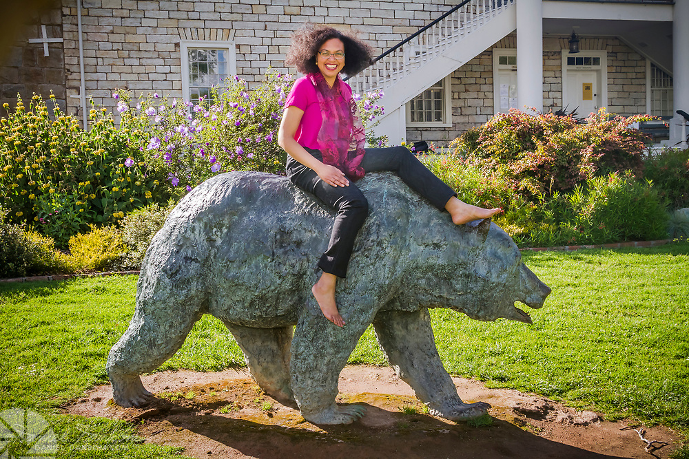 Beautiful young woman astride bear statue, Colton Hall, Monterey, California