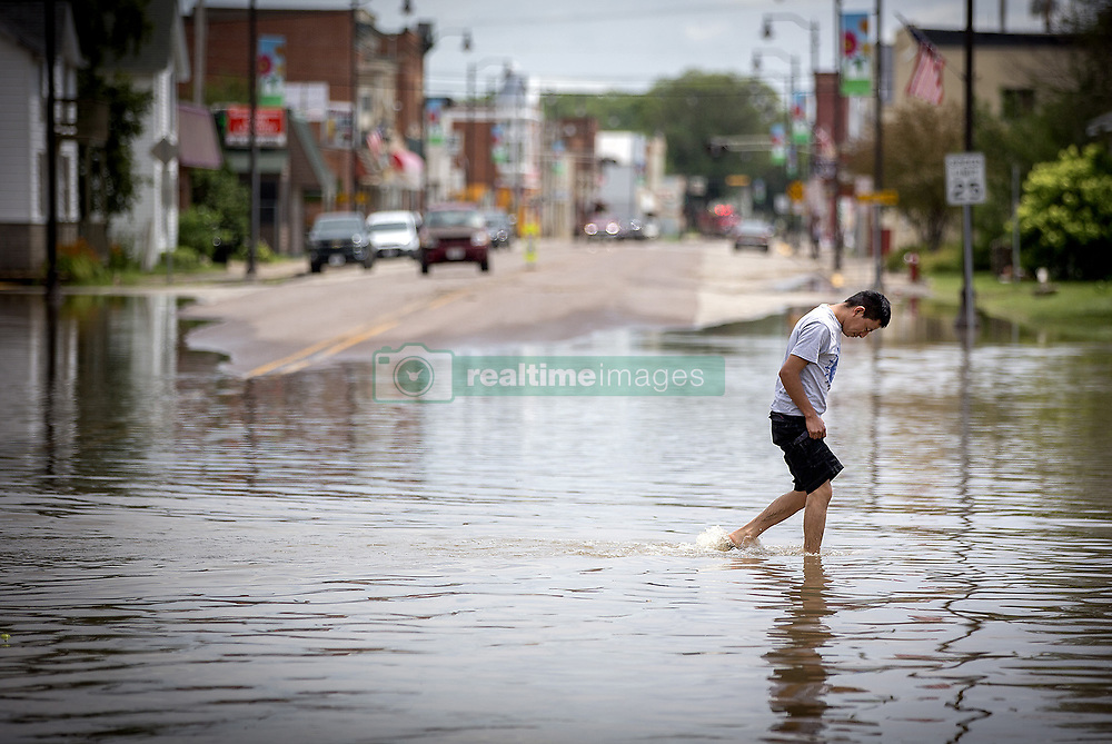 July 20, 2017 - Arcadia, WI, USA - Pedro Martinez makes his way across Main Street as many businesses were affected by flooding in downtown Arcadia, Wis., Thursday, July 20, 2017.   Much of the town was flooded after Wednesday night's rain flooding the Trempealeau River and Turton Creek. (Credit Image: © Elizabeth Flores/TNS via ZUMA Wire)