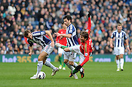 Swansea city's Michu is sent flying by WBA's Gareth McAuley (l) and Claudio Yacob (c)  Barclays Premier league, West Bromwich Albion v Swansea city at the Hawthorns stadium in West Bromwich, England on Saturday 9th March 2013.  pic by  Andrew Orchard, Andrew Orchard sports photography,