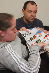 Wheelchair user being helped by carer doing craft activity at a resource for people with physical and sensory impairment.