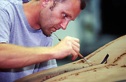 A worker shapes a clay model of a new Jaguar car. Jaguar design studios, Coventry, UK