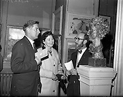 """27/04/1959<br /> 04/29/1959<br /> 27 April 1959<br /> Opening day of the R.H.A. Exhibition at the Royal Hibernian Academy, Dublin. Marshall C. Hutson, (right) Sunday's Well, Cork showing his exhibition """"Bean Si na Gaoithe"""" to Mr and Mrs Eddie Golden at the opening of the exhibition."""