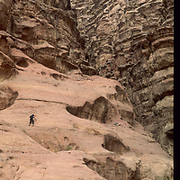 A rock climber in Jordan's Wadi Rum enters one of the labyrinth of side canyons in Rakabat Canyon on Jebel (Mount) Um Ishram.