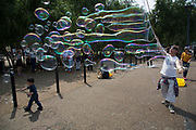 Bubble performers at Bankside, London. These bubble blowers are a common site along the South Bank making complex and large bubbles to delight audiences.