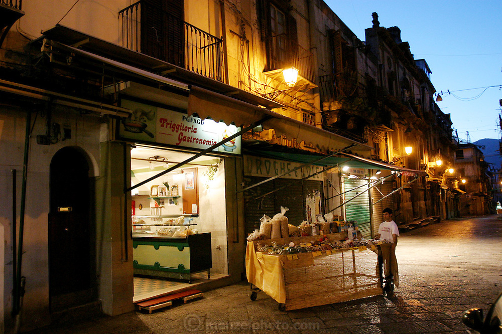 By 6:00 a.m., the fruit seller across the cobbled street from the Manzos' third-floor walk-up has already arranged half of his display. Living in the heart of Palermo Sicily's ancient Capo Market, the family is constantly enveloped in the cry and clamor of commerce; and, recently, the clatter of restoration work (scaffolding at the end of street around market gates). To Giuseppe, who grew up in this same Italian neighborhood, the hubbub is the sound of home. (Supporting image from the project Hungry Planet: What the World Eats.)
