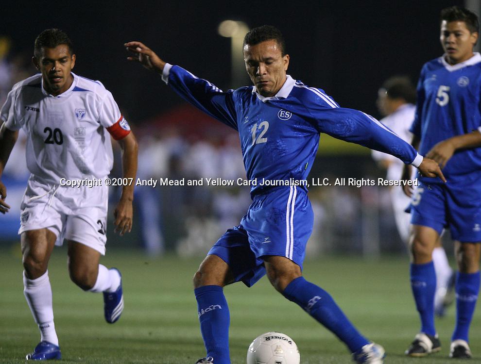 El Salvador's Ramiro Carballo (12) takes a shot as Jose Mardoqueo Henriquez (5) and Honduras's Amado Guevara (20) trail the play on Tuesday, March 27th, 2007 at SAS Stadium in Cary, North Carolina. The Honduras Men's National Team defeated El Salvador 2-0 in a men's international friendly.