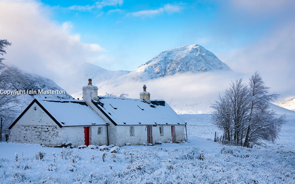 Glen Coe, Scotland, UK. 3 December 2020. A cold front has brought the first snowfall to the Scottish Highlands. Rannoch Moor and Glen Coe are covered in several inches of snow. Bright sunshine throughout the day created beautiful winter landscapes.  Pictured; Blackrock Cottage with mist covered Buachaille Etive Mor in the distance.  Iain Masterton/Alamy Live News