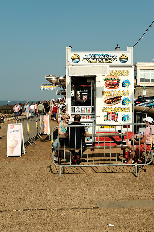 Spencers Beach Side Diner. On a busy Hunstanton seafront a fast food catering van has set up a picnic bench for customers to sit socially distanced in the summer sun. Taken on the last hot day of the Summer in Hunstanton Norfolk, the first summer in the UK during the COVID-19 pandemic.<br /> <br /> Photo by Jonathan J Fussell, COPYRIGHT 2020