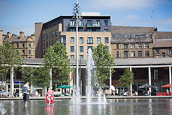 © Licensed to London News Pictures. 30/06/2015. Bradford UK. Families cool's off in the water fountains at Centenary square in Bradford. Britain is set to sizzle in temperatures of up to 34C (93F) today, with forecasters predicting the hottest day for several years. A tropical air mass moving from North Africa, Spain and Portugal means that we could be hotter than Rio de Janeiro. Photo credit : Andrew McCaren/LNP