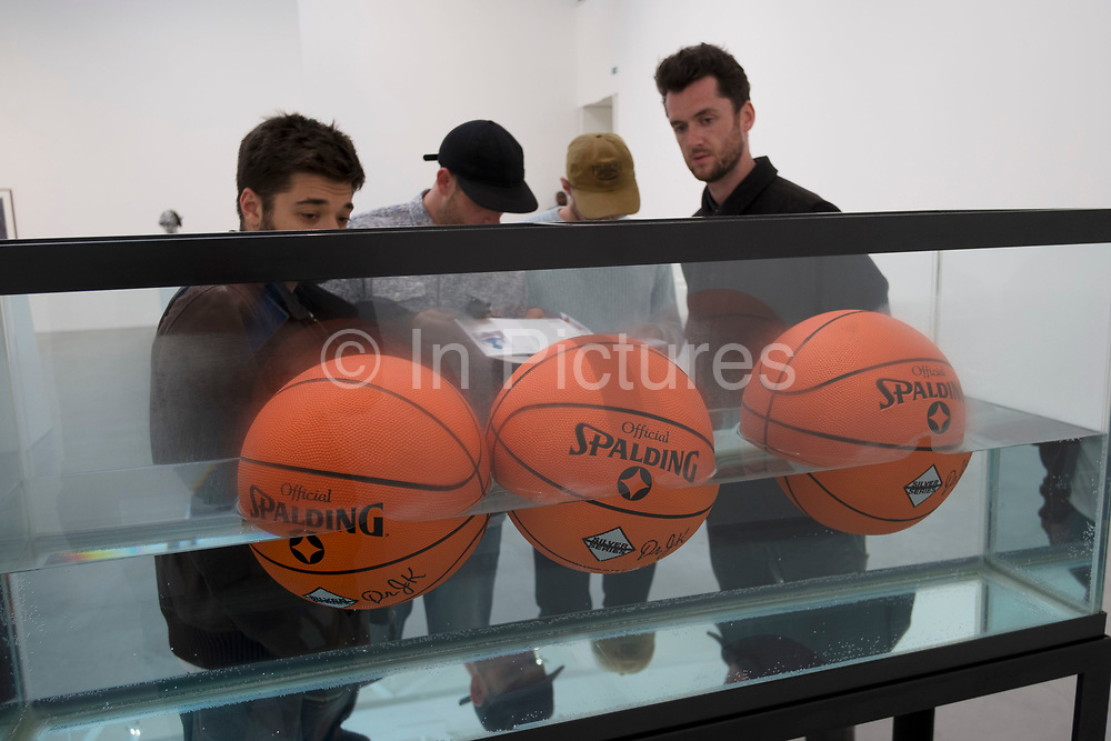 Three Ball 50/50 Tank basketballs at 'Jeff Koons Now' art show at Newport Street Gallery in London, England, United Kingdom. Jeff Koons is a modern American artist known for working with popular culture subjects and his reproductions of banal objects—such as balloon animals produced in stainless steel with mirror-finish surfaces. Newport Street Gallery presents exhibitions of work from Damien Hirst's art collection. Exhibitions vary between solo and group shows. (photo by Mike Kemp/In Pictures via Getty Images)