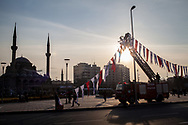 City council workers place Turkish flags and the council logo around the central Cumhurriyet Meydani in Kayseri, Turkey.