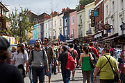 Walking down Portobello Road market, Notting Hill, West London. This famous Sunday market is when the antique stalls come out as well as the food stalls.