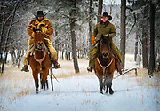 Two cowboys (Tommy and Wacy) riding their horses down a snowy road in a wooded area near New Haven ranch in Wyoming