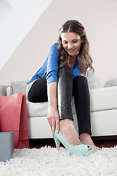 Portrait of young woman sitting on couch at home trying on new high heels
