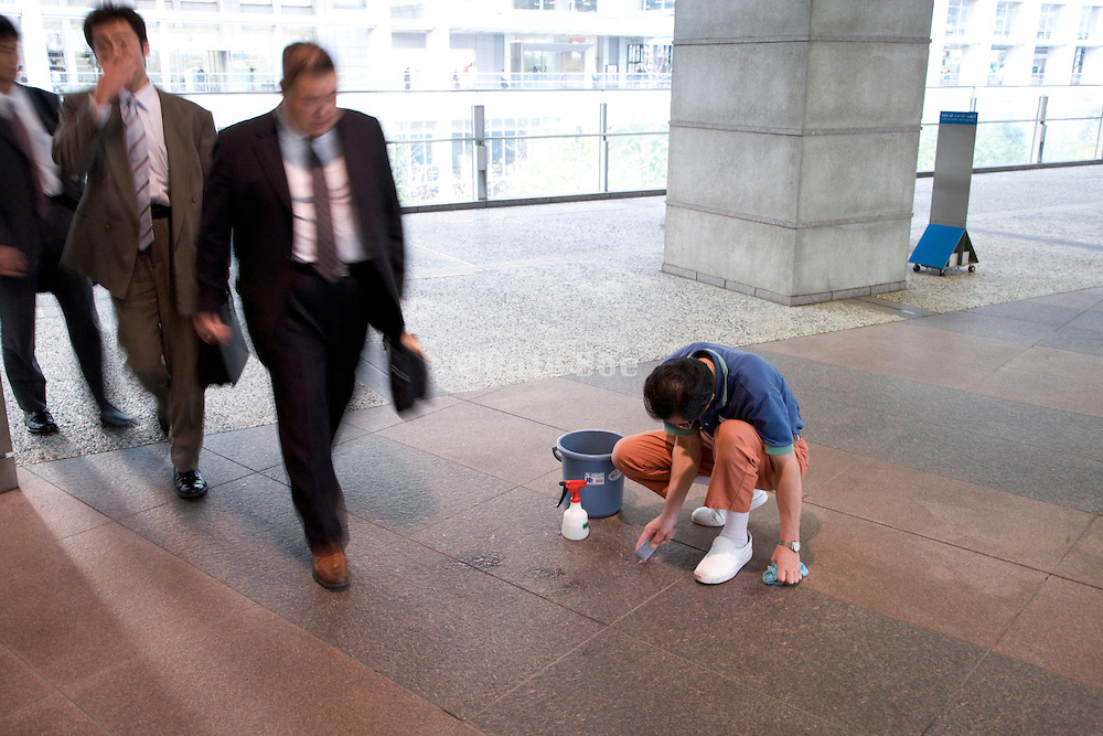 man cleaning floor by hand while some businessmen walk by Japan