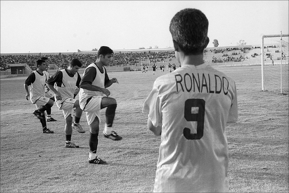 Players warm up during a match between the Iraqi national football (soccer) team and the Kurdistan all-city team, in Erbil, Iraq, in the first post-war match. The Iraqi team won, 3-0, but the fans still cheered them.
