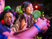 31 DECEMBER 2013 - BANGKOK, THAILAND: A child enjoys a magic act at the Bangkok New Year's Eve party in Ratchaprasong Intersection. Hundreds of thousands of people pack into the Ratchaprasong Intersection in Bangkok for the city's annual New Year's Eve countdown. Many Thais go the Erawan Shrine and Wat Pathum Wanaram near the intersection to pray and make merit.     PHOTO BY JACK KURTZ